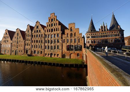 LUBECK, GERMANY - DECEMBER 30, 2016: People at Salt storehouses and Holsten Gate. Because of its extensive Brick Gothic architecture, the city is listed by UNESCO as a World Heritage Site