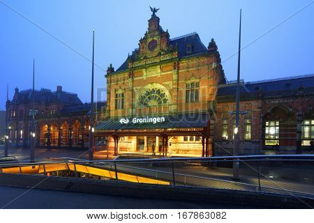 GRONINGEN, NETHERLANDS -DECEMBER 31, 2016: People in front of the train station in evening. The station building was designed by Izaak Gosschalk, completed in 1896, and most recently restored in 2000