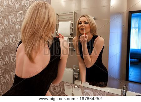A beautiful young blond woman putting on makeup in the bathroom and getting ready to go out