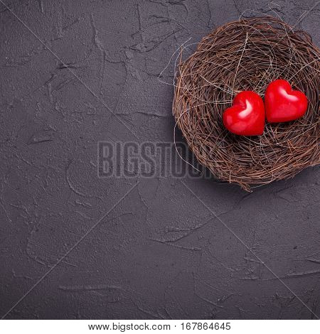 Hearts in nest on black slate background. Flat lay.Top view. St. Valentine day background. Place for text. Square image.