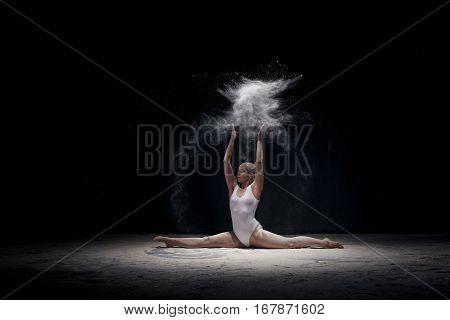 Slender girl sitting in split in cloud of white dust studio shot