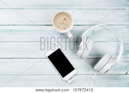 Smartphone, headphones and coffee cup on rustic wooden table. Top view