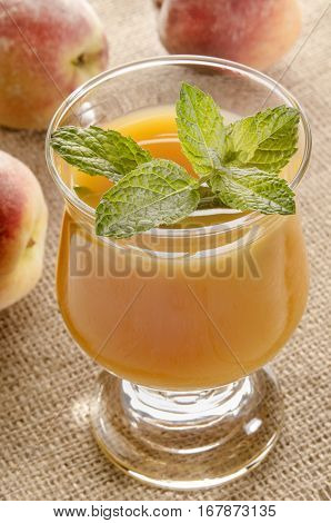 cold peach juice with mint leaf in a glass
