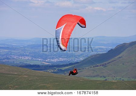 Paraglider flying his wing in the Brecon Beacons