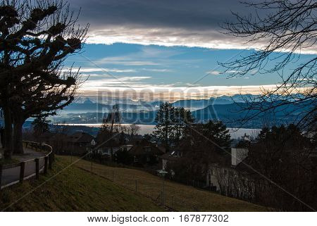 Blue sky with white and gray clouds overlooking the lake of Zurich with the snowy alps / mountains in the backgroudn