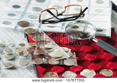 Different collector's coins with a magnifying glass and glasses soft focus background