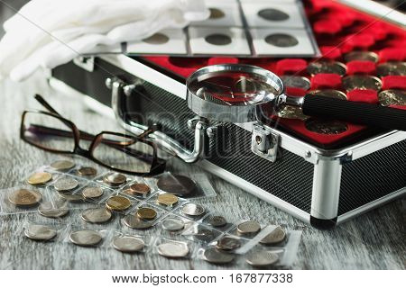 Box with collector's coins magnifying glass and glasses soft focus background