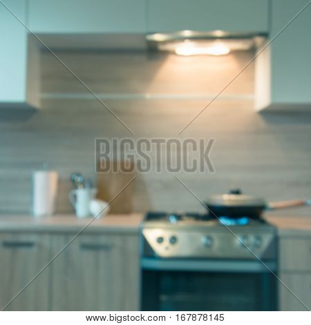 Blurred background. Modern kitchen with cooking on gas and space for you. Toned image.