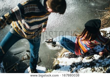 Young woman using a shoe breaks the ice while standing on the shore with boyfriend. Winter and spring coming lifestyle concept