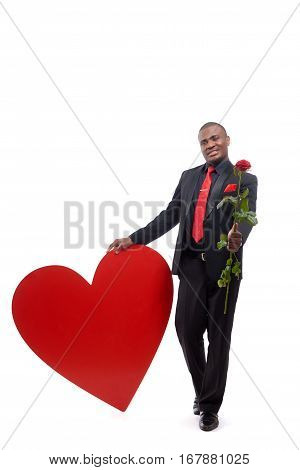 Full lenght portrait of happy african man giving and presenting at camera red rose,  flower for girlfriend to Valentine. Handsome male wearing black suite and red tie, leaning on big heart in studio.