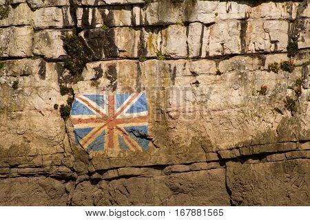 British Union Jack flag painted on the Limestone Cliffs of the River Wye opposite Chepstow with Union Jack flag beside it.