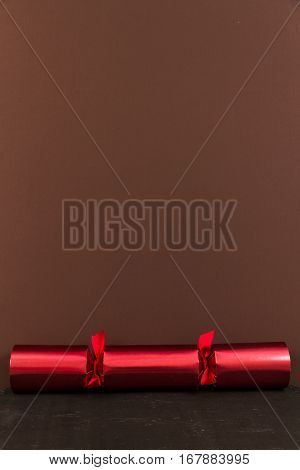 Red Christmas cracker with brown space above it.
