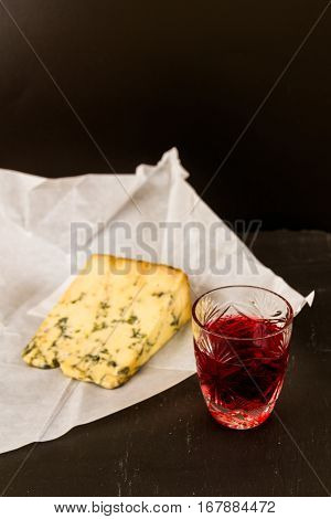 Shot glass with slow gin beside a wedge of stilton cheese unwrapped greaseproof paper.