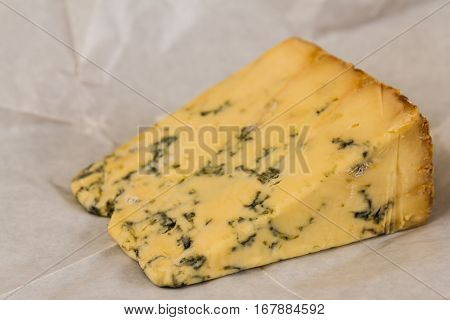 stilton cheese resting on unwrapped greaseproof paper.