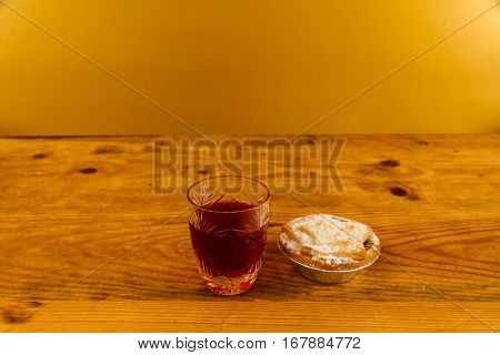 Shot glass with slow gin and mince pie on wooden table.