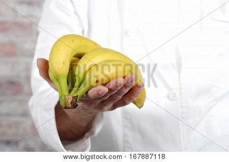 close up of a hand man holding banana