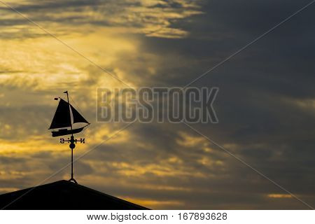 A colorful sunset over water with a weather vane in the foreground