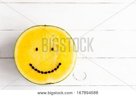 jellow watermelon with smile on white wooden background top view flat lay