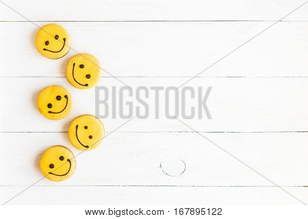 Smiley faces on wooden white background. Food. Glazed cookies. Top view flat lay poster