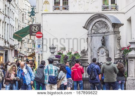 BRUSSELS BELGIUM - AUGUST 22 2014: People looking at Manneken Pis statue in Brussels. Statue of a pissing boy an iconic symbol of the Belgian Capital