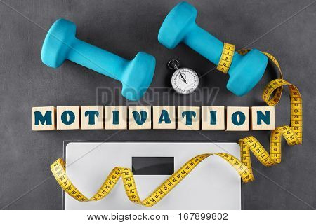 Sport concept. Word MOTIVATION of cubes with training equipment and scales on gray background