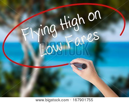 Woman Hand Writing Flying High On Low Fares With Black Marker On Visual Screen