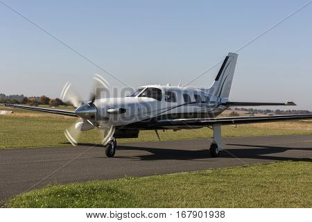 Private small single turboprop aircraft on airport runway. Small sports plane scrolls on the runway on a sunny day