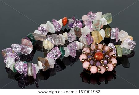 closeup brooch and beads from crystals of amethyst fluorite jasper carnelian and rose quartz on black table.