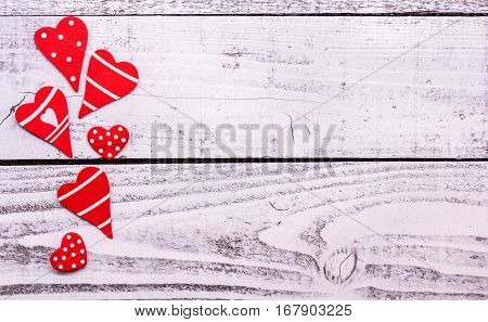 Valentine's day and Sweetest day love concept. Red hearts border on rustic white wood boards. Holiday background with copy space.