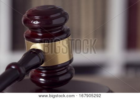 Close up of a judge gavel and law books in the background of a courtroom. Selective focus