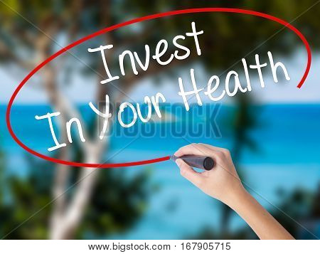 Woman Hand Writing Invest In Your Health With Black Marker On Visual Screen.
