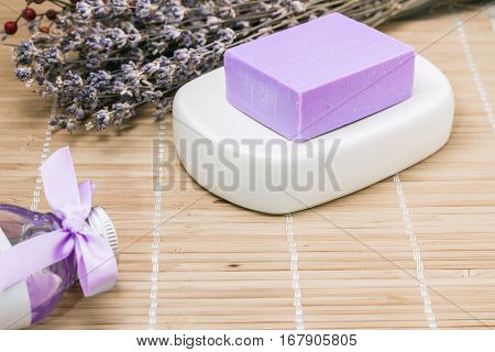 Bar of natural lavender soap on white ceramic soap dish and a bottle with shower gel over beige bamboo mat background