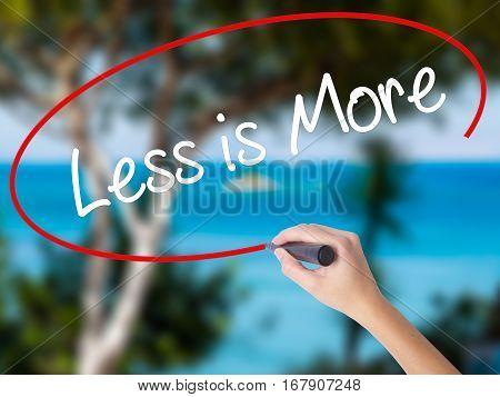 Woman Hand Writing Less Is More With Black Marker On Visual Screen