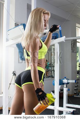 Active sexy woman in a sport green clothes stands at a sports gym equipment. Sports nutrition. Amino acids. Beautiful body. Fitness. Shiny skin
