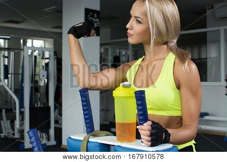 Active sexy blond woman in sportswear sitting on the sports equipment shows inflated biceps. Gym. Sports nutrition. Amino acids. Strength of will. Shiny skin