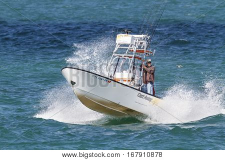 Tampa Bay, Florida, USA - February 28, 2010: Sport fishing boat hammering across choppy Tampa Bay