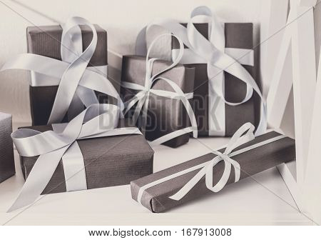 Elegant gift boxes with satin ribbon wrapped in paper. Closeup on white shelves in modern interior. Any holiday background with copy space. Christmas, birthday or valentine concept. High key