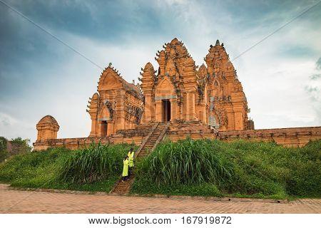 Champa Temple - Hidu Tower In Asia. Vietnamese Women In Traditional Dress Ao Dai Walking Toward The