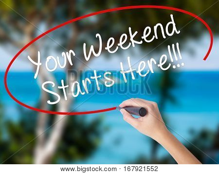 Woman Hand Writing Your Weekend Starts Here!!! With Black Marker On Visual Screen