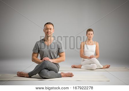 Young athletic man and woman sitting in Gomukhasana Cow face pose on yoga mats