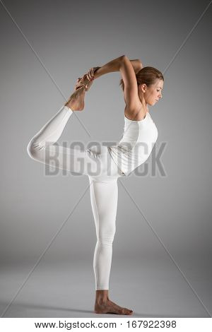 Woman practicing yoga standing in Natarajasana Lord of the Dance posture