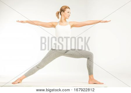 Woman practicing yoga standing in variation of Warrior 2 posture or Virabhadrasana Two pose