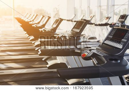 Modern gym interior equipment detail. Fitness treadmill's control panels closeup for fitness cardio training in evening light. Healthy lifestyle concept