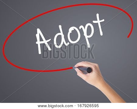 Woman Hand Writing Adopt  With Black Marker On Visual Screen
