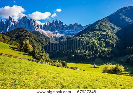 Little picturesque church of Santa Maddalena in Val di Funes.  Sunny autumn day in Dolomites, Tirol. Rocky peaks and forested mountains surrounded by green Alpine meadows