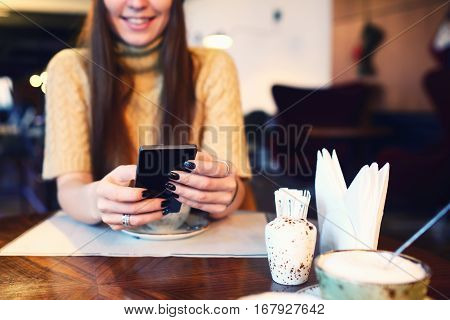 Close up of women's hands holding cell telephone with blank copy space scree for your advertising text message or promotional content, hipster girl watching video on mobile phone during coffee break.