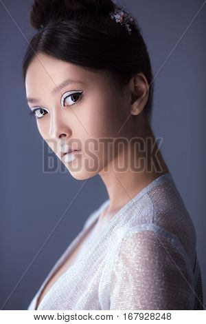 Creative art make-up and hairstyle. Portrait of asian young woman. Beautiful young model Japanese style girl in silver urban clothes with conceptual hairstyle and make-up against gray copy-space background looking at camera.