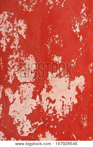 Grunge background with old stucco wall texture of beige color and cracked paint of red color