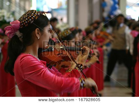 Ashgabat, Turkmenistan - 21 August 2008 - Woman in traditional Turkmen dress playing the violin at the national festival in August 21, 2008 in Ashgabat, Turkmenistan
