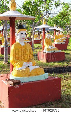 Rows of old stone statues of Buddha under umbrella, Bodhi Ta Taung temple complex (Thousand Buddhas garden), Monywa, Sagaing Region, Myanmar (Burma)